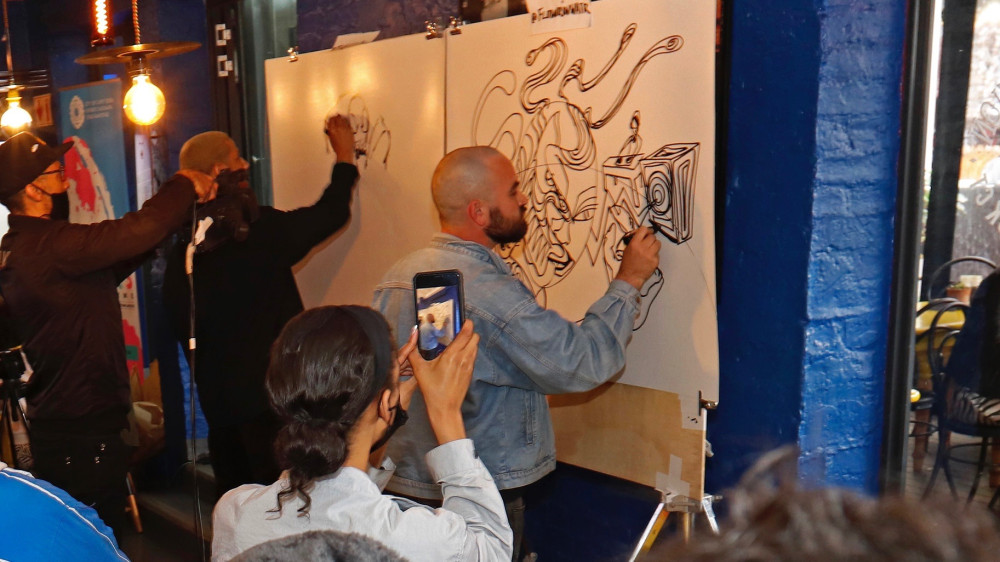 """Artists cross pens during a """"Draw Off"""" at the pop-up Comic Con Cape Town event Oct. 2."""