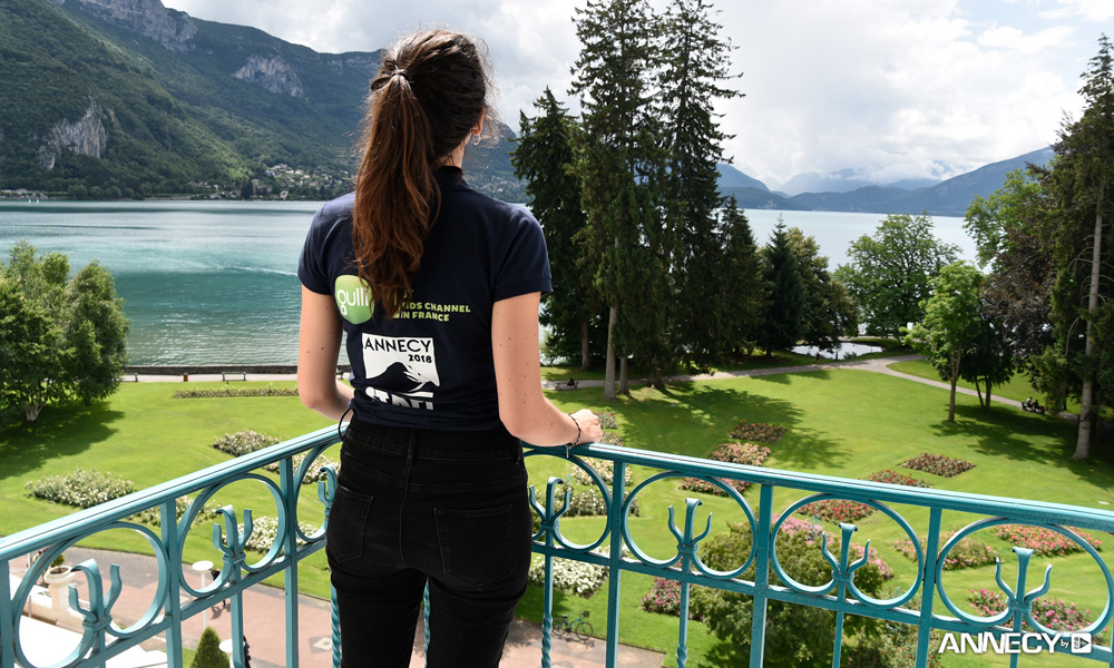 An Annecy 2018 event staffer takes in the view from The Imperial Palace. [Photo : F. Blin/CITIA]