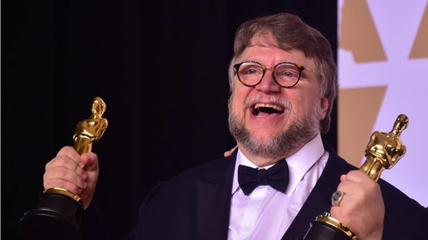 Guillermo del Toro hoists his two awards for The Shape of Water at the 2018 Oscars. [© Photo AFP, Frederic J. Brown]
