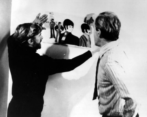 Jack Stokes (bearded), who directed The Beatles TV series, looking at a Yellow Submarine cel with George Dunning.