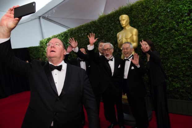 John Lasseter (left) takes a selfie with Honorary Oscar recipient Hayao Miyazaki (center), Toshio Suzuki and guests at the Governor's Awards in 2014. [Photo: Academy of Motion Pictures]