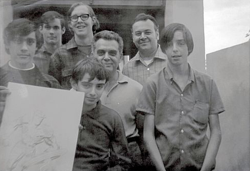 Photo of the very first committee members of the San Diego Comic-Con (except for Mike Towry, who is not pictured). It was taken in the fall of 1969 at the home of Jack Kirby. Left to right are: Dan Stewart (holding drawing), Bob Sourk, Richard Alf, Barry Alfonso (in front, holding drawing), Jack Kirby, Shel Dorf and Wayne Kincaid.