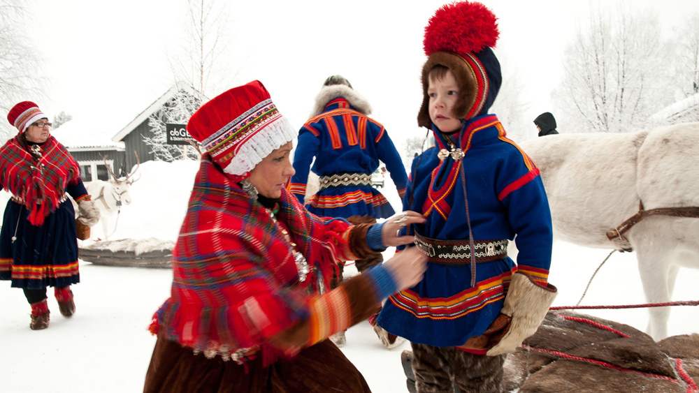 A Sami family (with reindeer!) in traditional dress. [Photo: Lola Akinmade Åkerström/imagebank.sweden.se]